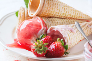 Close up of wafer cones with strawberry ice cream with syrup, mint and fresh strawberries served on white plate over white textile. Top view.